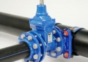 Water supply connection with flanged saddles and valve